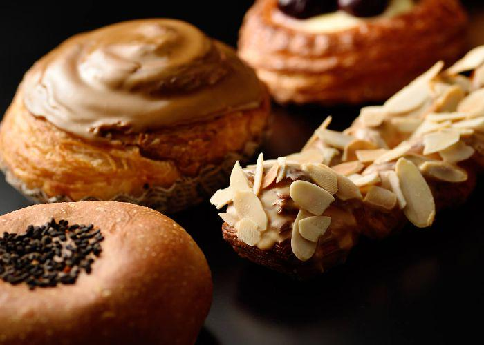 An array of bread from Pompadour, a French-inspired Japanese bakery. One bread, anpan, is topped with black sesame seeds,