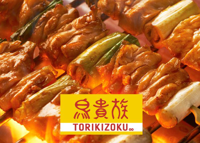 Glistening skewers of meat grilling over charcoals with the Torikizoku logo overlaid on top