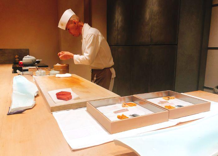 Omakase sushi chef dressed in white preparing sushi for guests