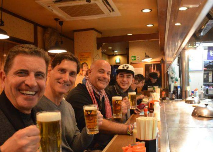 Smiling men raising glasses of beer at a teppanyaki restaurant in Shibuya during a food tour