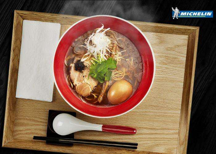 """A red bowl of ramen on a wooden tray, with the word """"Michelin"""" in the upper right corner of the image, referring to the Michelin-starred status of Tsuta, a ramen restaurant in Tokyo"""