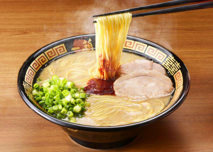 Bowl of Ichiran Ramen, one of the best ramen in Tokyo, with a spicy red sauce in the center of thin noodles in a tonkotsu broth, with a pop of green from the chopped scallions and thinly-sliced chashu pork.