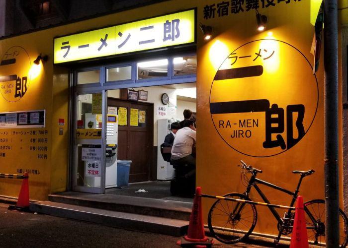 "Exterior of Ramen Jiro Shinjuku Kabukicho, glowing yellow shop sign and vibrantly yellow-painted walls, showcasing the sign ""RA-MEN JIRO"""