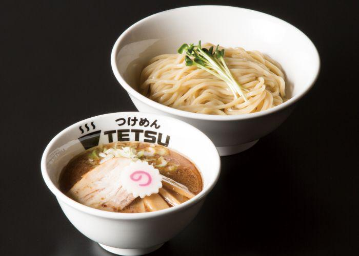 Tsukemen ramen from Tetsu: two bowls, one of ramen noodles and another with broth and chashu pork, against a dark background.