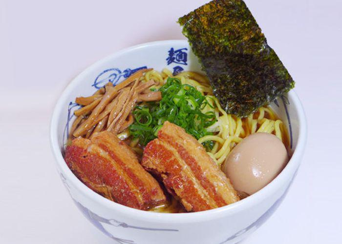 Large bowl of ramen, with huge strips of meat and an egg, from Menya Musashi against a white background