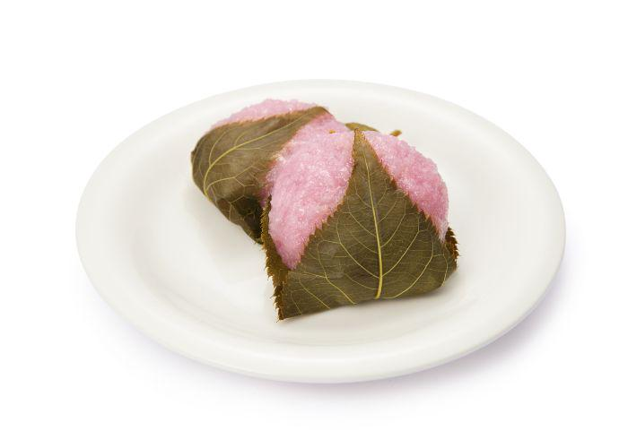 sakura mochi, a pounded rice cake colored pink, wrapped in a green leaf