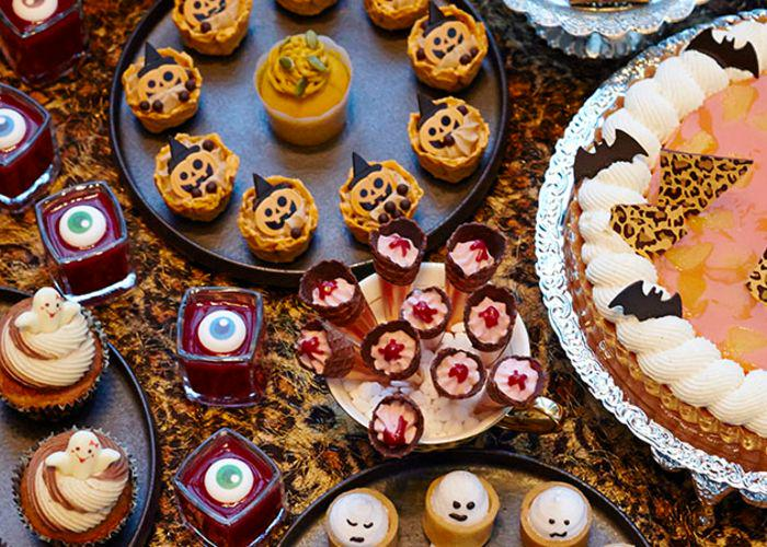 A sweets buffet with ghost meringues, tarts, cupcakes, and Halloween-themed desserts