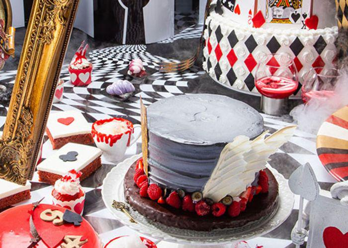Alice in Wonderland Mad Tea Party-themed buffet with playing cards, red, white, and black checkers, and a cake shaped like the Mad Hatter's hat