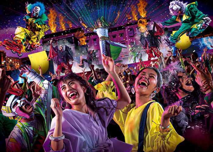 Two women dancing among a crowd of zombies, monsters, clowns, and brightly lit costumed performers onstage