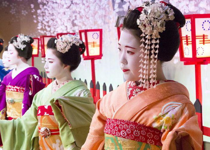 Maiko and geiko drssed in colorful Japanese kimono, with their faces painted white and lips red
