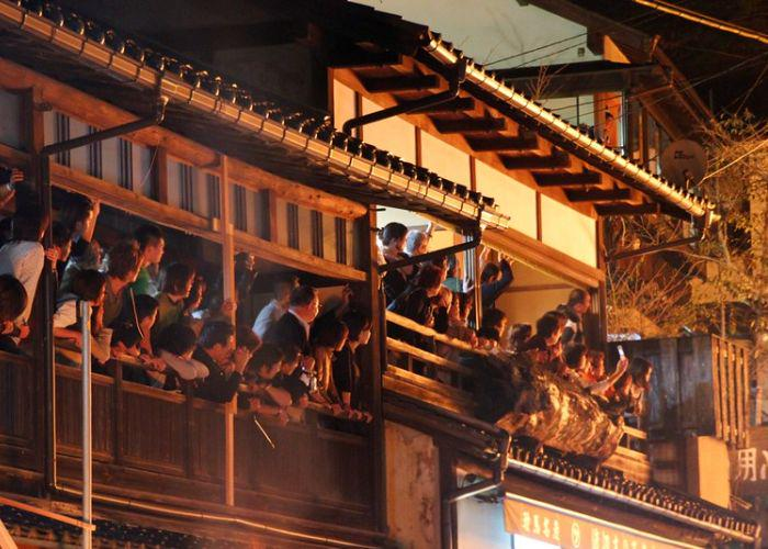 Golden light from the fire illuminates the crowd of people gathered on balconies to watch the Kurama Fire Festival proceeding below