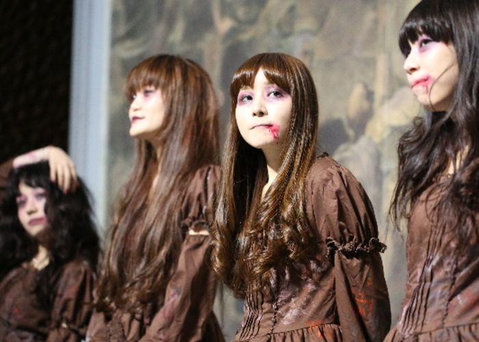 Women dressed upin tattered brown costumes with fake blood dripping from their mouths pose for the Halloween costume contest