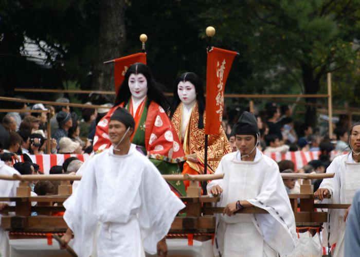 Two women, dressed in red and gold traditional Japanese dress, are carried on a structure by men dressed in white during the Jidai Matsuri Festival