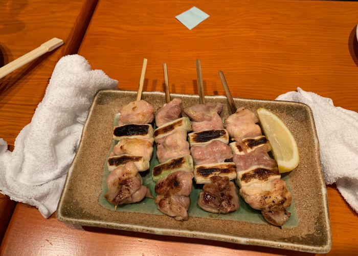 Yakitori skewers on a rectangular plate, with a side of lemon wedge, grilled and charred