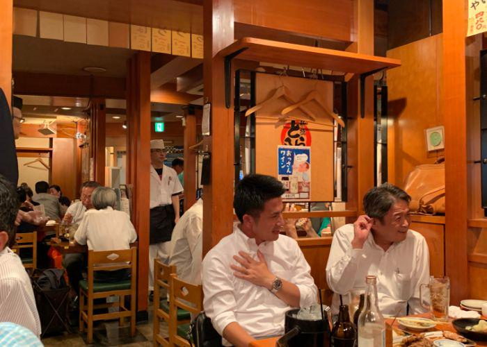 Japanese businessmen wearing white collared shirts sit at an izakaya