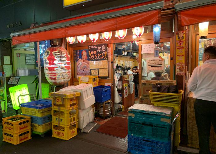 The exterior of a Tokyo izakaya, with red lantern outside, and yellow Kirin boxes stacked outside the door.