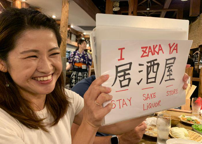 "A Japanaese woman holds up a sign with the word ""izakaya"" written in Japanese and romaji, explaining the meaning of the word"