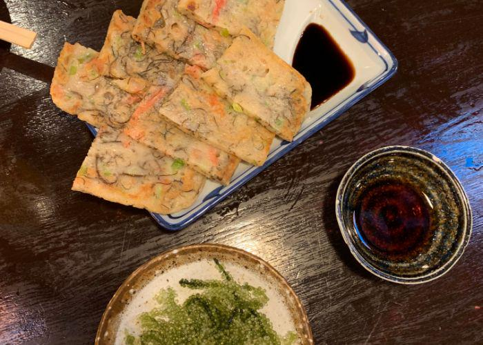"Two Okinawan specialty dishes: Okinawan flat, savory pancake and green umibudo, also known as ""sea grapes"""