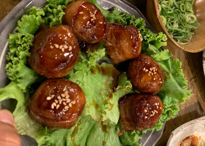 A bed of lettuce upon which several balls of glazed meat, topped with sesame seeds, are resting