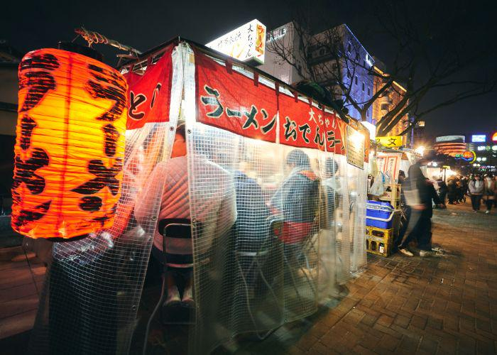 """Red glowing lantern with the word """"ramen"""" written on it in Japanese katakana, marking this Fukuoka yatai street food stall. The backs of people enjoying their ramen are visible from under the plastic tarp covering the street food stand."""