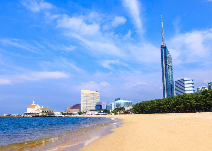The vibrant blue waters of Fukuoka Bay meet the sandy beach, with a skyline of tall modern buildings against a blue sky and white wispy clouds