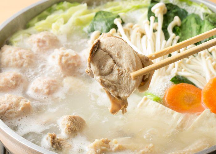 Mizutaki, a Fukuoka hot pot specialty. Pieces of chicken, carrot, mushrooms, and green veggies swim in a chicken broth. Two chopsticks hold up a piece of cooked chicken