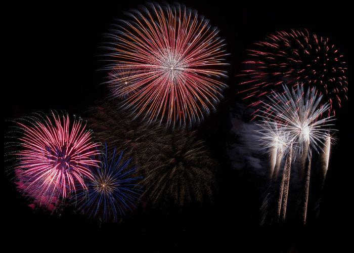 Pink, blue, orange, and white firework bursts in the black sky