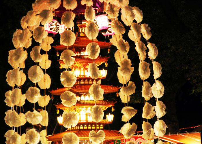 A tall red pagoda towers in the background against a black night sky, lit by lanterns