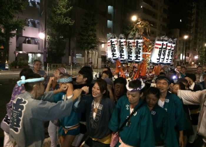 Several people carrying a mikoshi, a small portable shrine, during the Yanaka Matsuri