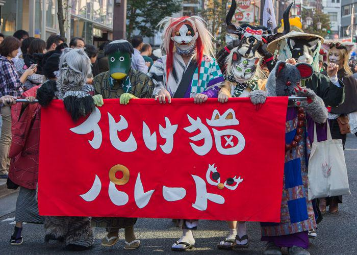 People dressed as cats, wearing cat masks and kimonos, and fuzzy cat costumes, carry a sign for Kagurazaka Bakeneko Festival