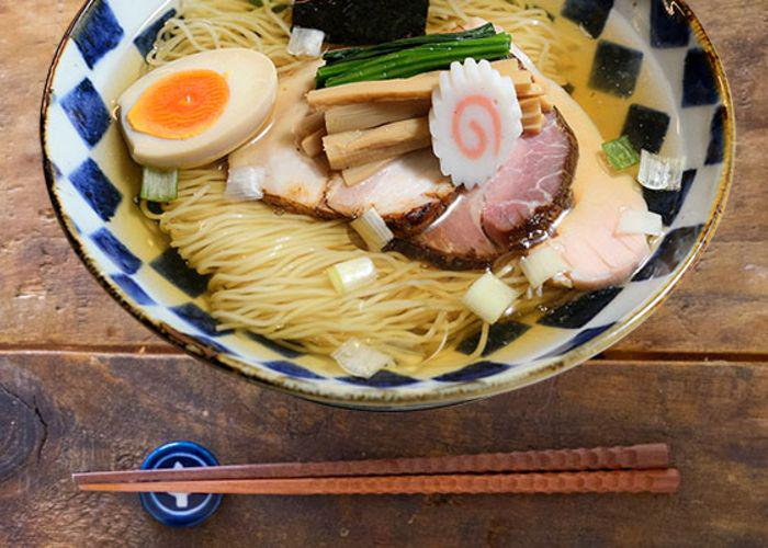 Bowl of ramen, with thin straight noodles topped by egg, naruto, chashu pork, menma