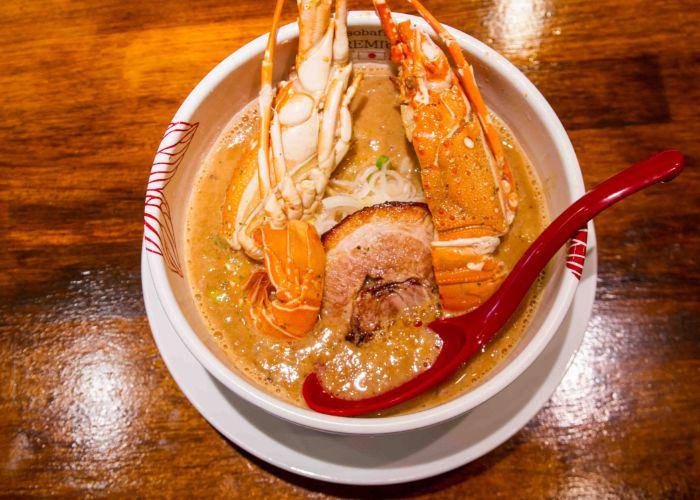 Aerial view of a white bowl of lobster ramen, filled with glistening orange soup and topped by large lobster claws