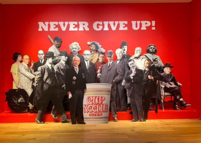 """Cup Noodles Museum Interior, with a life-size cutout of Momofuku Ando, the creator of Nissin's Cup Noodle, and many other famous inventors and historical figures, with the phrase """"Never Give Up!"""" written on the wall"""