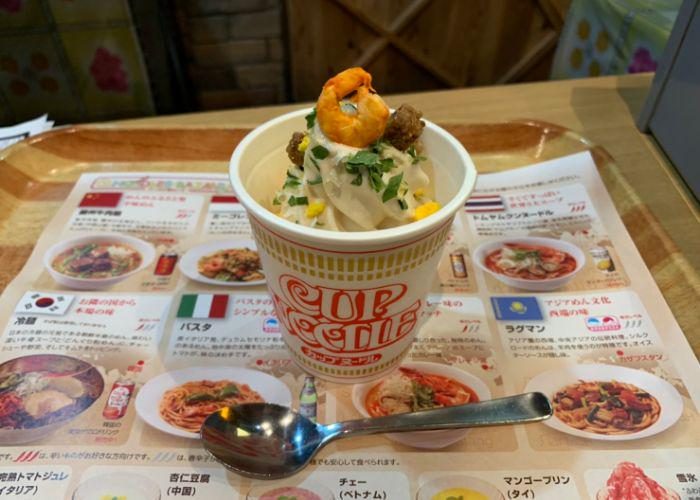 Soft Serve Ice Cream is served in a Cup Noodle cup at the at Cup Noodles Museum, topped by a shrimp