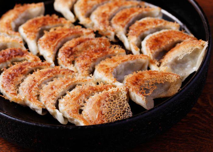 Pan-fried gyoza dumplings nestled in a dark iron skillet, with crispy brown bits facing upwards