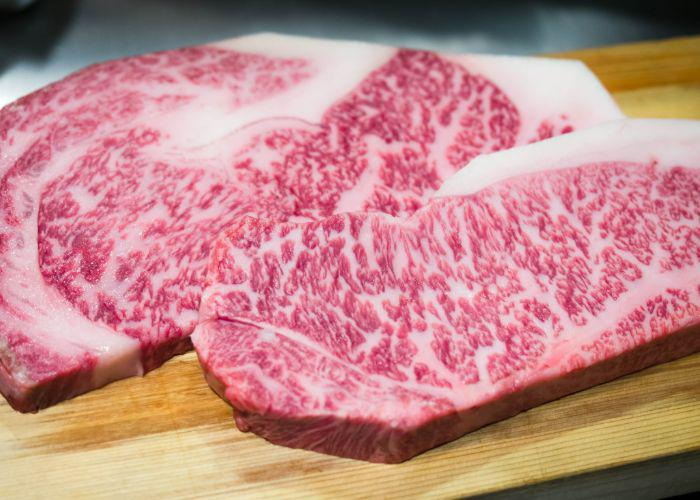 Two cuts of raw Kobe and wagyu beef on a wooden cutting board