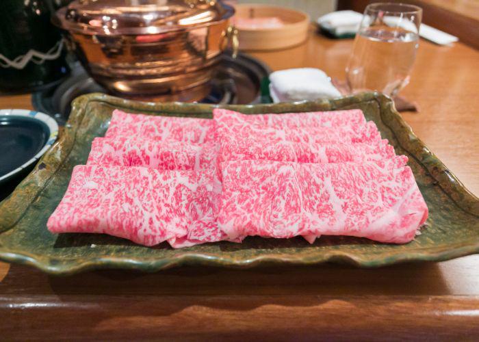 A plate of thinly sliced folded Kobe beef for shabu shabu