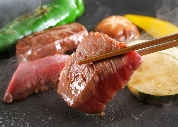 A pair of chopsticks holding a piece of cooked Kobe beefsteak