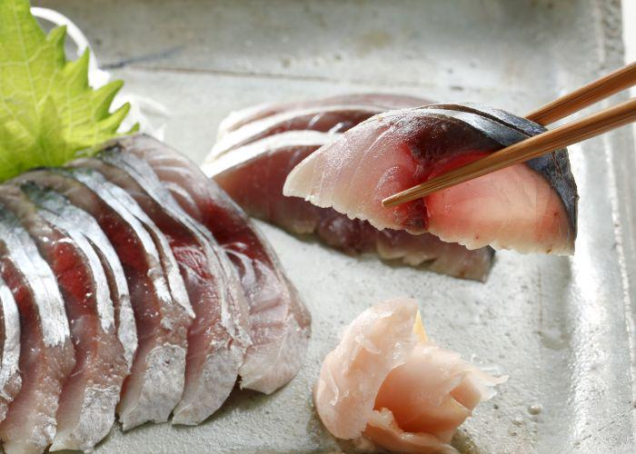 A neatly lined up row of saba (mackerel) sashimi slices with a silver skin, placed on a plate. A hand holding chopsticks picks up one piece of the sashimi