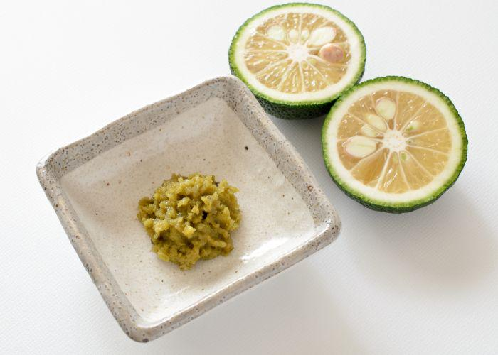 Yuzu kosho, a Japanese condiment that is made of the citrus fruit, yuzu. It is a mashed, green condiment on a plate, next to two halves of a sliced yuzu
