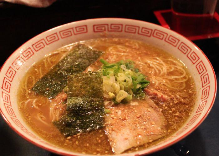 A bowl of Hakata ramen with seaweed, sesame, noodles and pork
