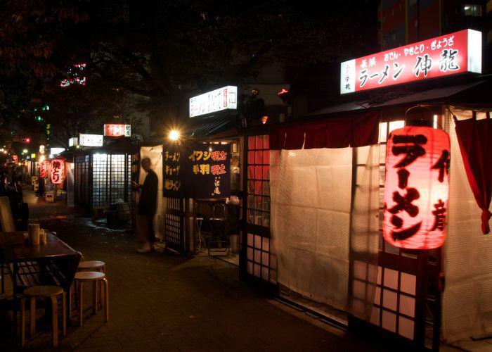 A night time scene of lit yatai street food stalls