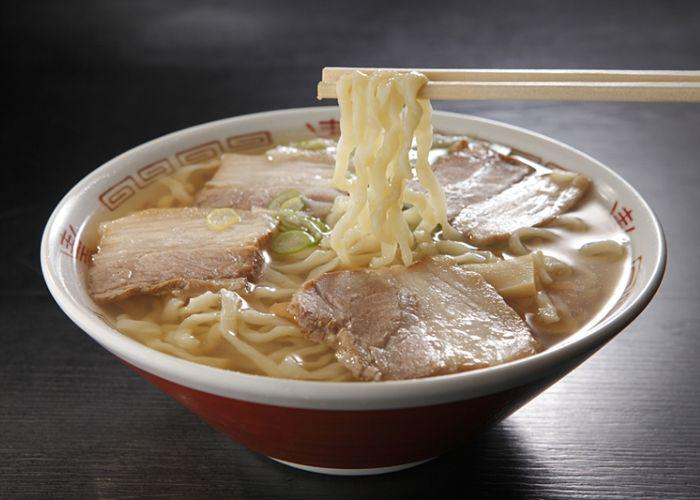 A steaming bowl of Kitakata ramen with chopsticks holding the noodles and slices of pork on top