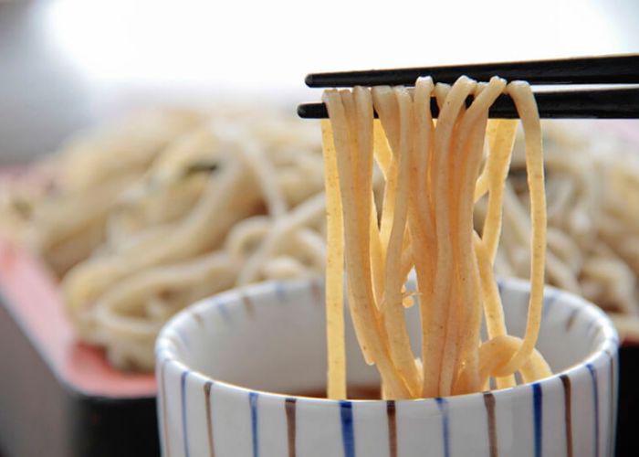 A pair of black chopsticks holding soba noodles