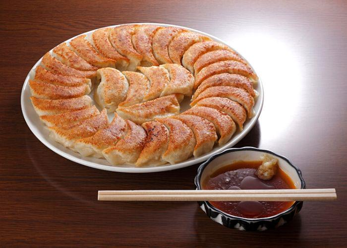 A platter of Emban gyoza dumplings on a table with a brown dipping sauce and chopsticks
