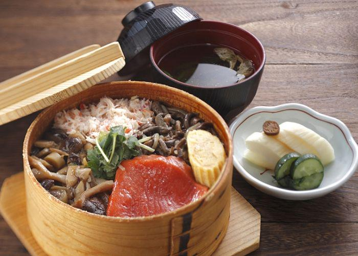 A wooden box filled with seasonal foods such as mushrooms on a table with other dishes such as soup and a dish of cucumber and bamboo shoots