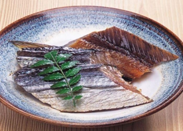 Dried pieces of herring on a blue plate