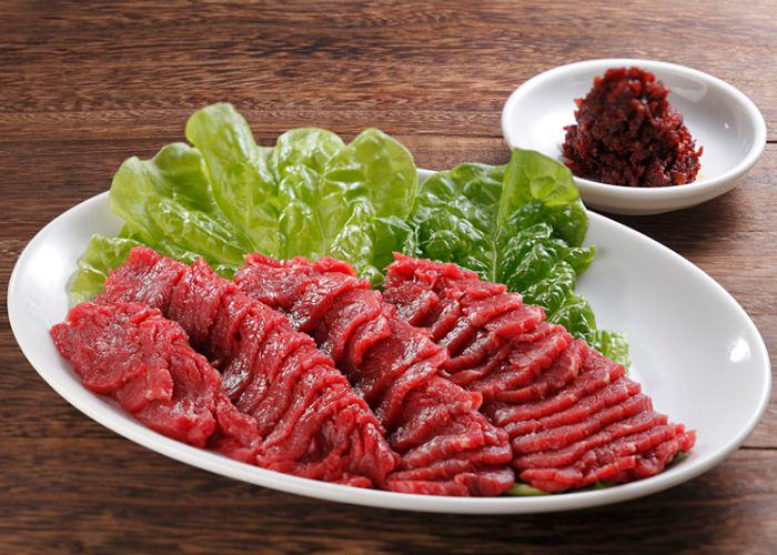 A plate of raw horsemeat with lettuce on the side and a dish of hot soybean paste on the side