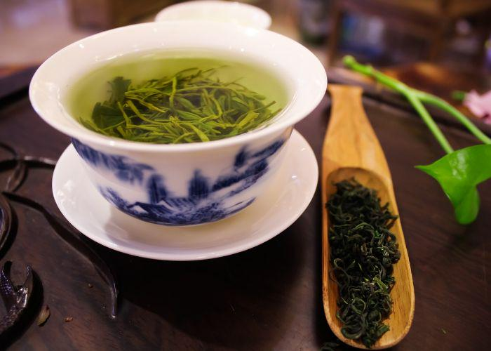 A white china tea cup filled with green tea and tea leaves sat on a brown tabletop