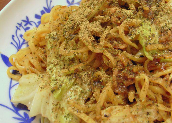 A plate full of yakisoba noodles with cabbage and dried sardines on top